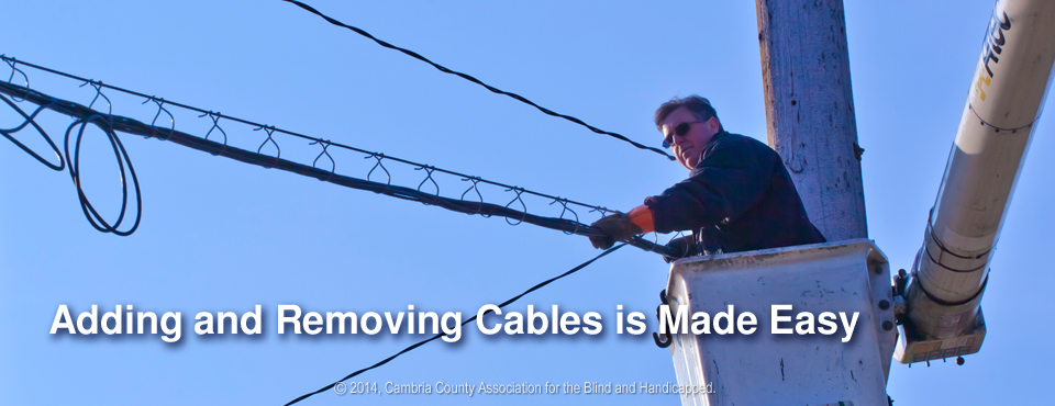 Photo of worker pulling cables through CAB Cable Rings and Saddles